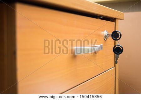 Closed drawer of his desk with the keys in the lock