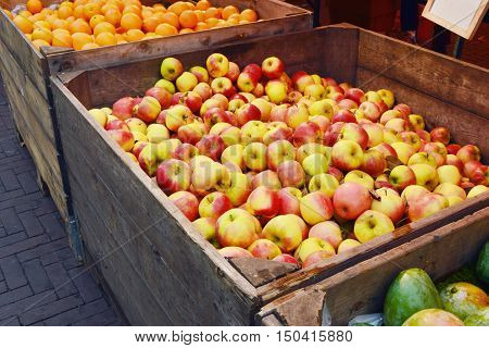many apples and oranges in big woodden box at market