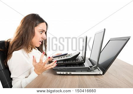 Businesswoman with an angry expression and stressed front of three laptops