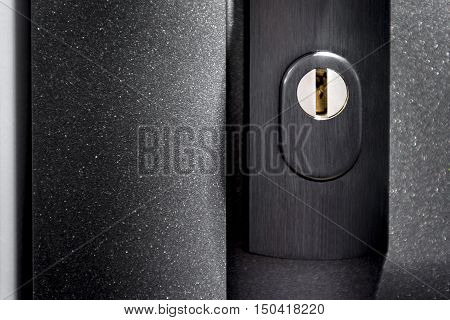 Part of door with keyhole on black metalic surface