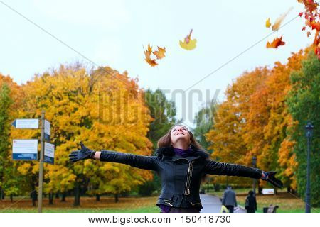 One girl walks in autumn park, throwing foliage into sky. Girl looks into sky