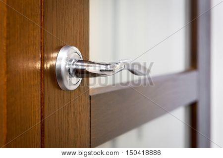 Part of wooden closed door with gold door-handle