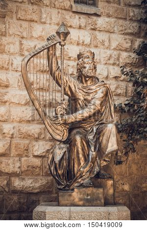 JERUSALEM ISRAEL - OCTOBER 5: The statue of King David playing the harp near entrance to his tomb on Mount Zion in Jerusalem Israel on October 5 2016