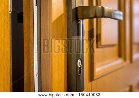 Part of wooden open door with metal door-handle