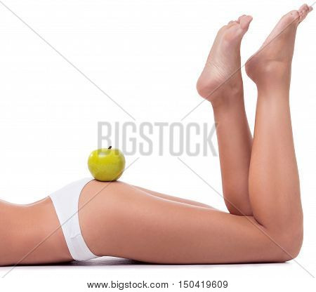 Cropped image of beautiful slim girl in white lingerie posing lying with an apple on her booty isolated on white