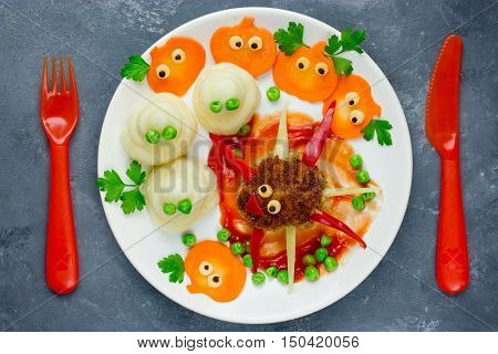 Creative idea for baby dinner or lunch - funny spider meatball with colorful vegetables garnish shaped ghost and carrot pumpkin. Concept of healthy meal food for children