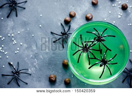Green witch drink or jelly in glass with spiders Halloween food idea top view