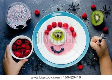 Halloween dessert recipe scary fun and tasty one-eyed monster jelly panna cotta with fruit. Creative idea for kids party