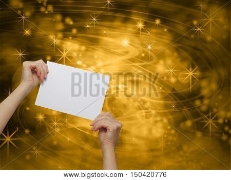 Celebrate Gold Message Card  - female hands holding up a white blank promotion card on a deep brown and golden swishing lines and sparkling stars background