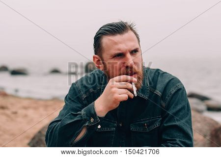 Serious bearded man smoking a cigarette on the beach. bearded hipster on the beach. Close-up portrait