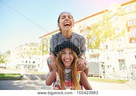 Teen girl on back of happy friend in tie dye shirt and cute black hat giggling in urban setting outdoors