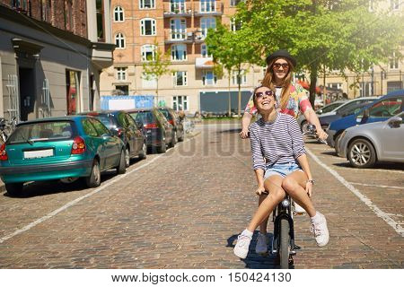 Two young girlfriends having fun on a bicycle in a cobbled urban street with one hitching a ride on the handlebars laughing happily