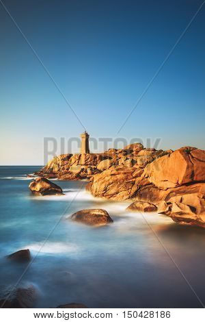 Ploumanach Mean Ruz lighthouse red sunset in pink granite coast Perros Guirec Brittany France. Long exposure.