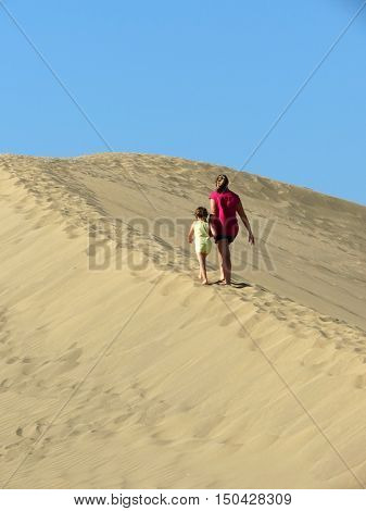 mother and daughter walking on sand dune