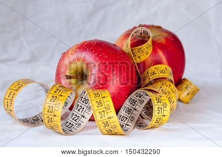 Two red apples and a yellow tape measure
