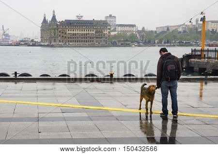 Istanbul, Turkey - April 18, 2014: Istanbul Kadikoy Steamboat pier and Haydarpasa train station building. People walking in the rain pier. Strait of Istanbul Kadikoy Pier ferries are the most popular form of public transport in Istanbul.