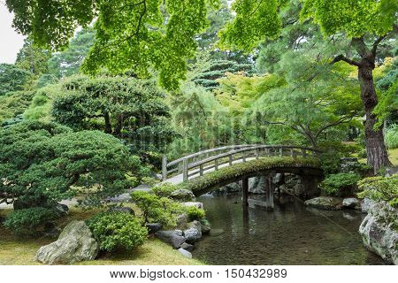 Kyoto Japan - September 14 2016: Part of the Japanese garden at the Imperial palace showing bow bridge pond and multiple trees.