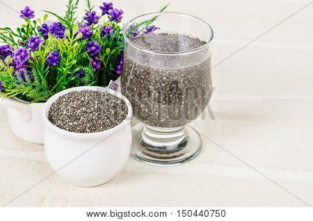 Dry Chai seed super food soaked in clear glass of water on tablecloth.