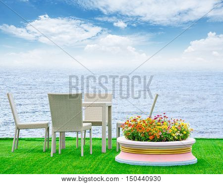Deck Chairs and flower pot on green grass byside beach sea with blue sky.
