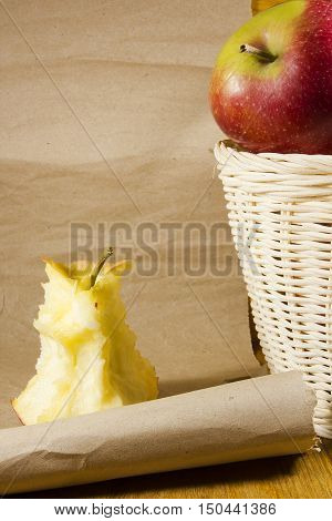 Apple core and a basket with apples on the background paper scroll