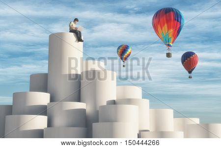 Man sitting on top of cylinders using a laptop while hot air balloons flying arround the sky. This is a 3d render illustration
