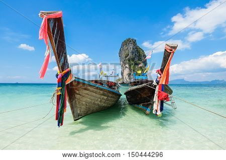 Long tail boats on crystal clear water at Poda Island, Krabi Thailand