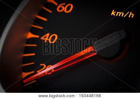 Car odometer with a red arrow closeup.