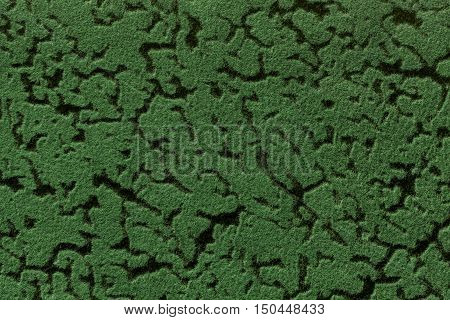 Green background from a soft upholstery textile material closeup. Fabric with natural texture. Cloth backdrop.