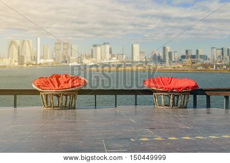 Chairs made of rattan and upholstery fabrics in red on wooden terrace with the backdrop of the lake and city.