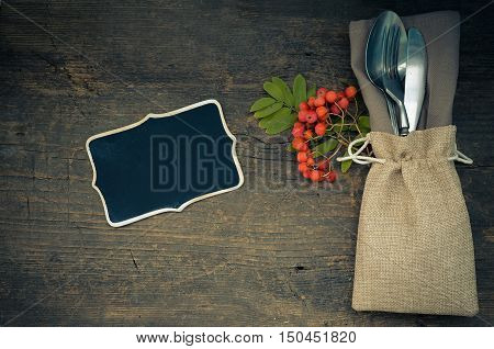 Thanksgiving autumn place setting with cutlery on wooden background with chalkboard for text. Table setting on the autumn background. Thanksgiving holidays background concept. Copy space. Top view.