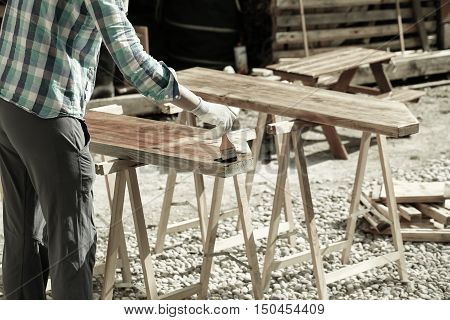 Worker applying and protecting garden furniture with fresh wood treatment paint. Outdoor protection carpentry hard at work home improvement do-it-yourself concept.