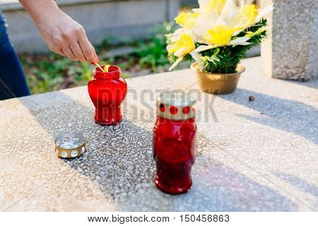 A Woman Lights A Candle At The Grave.