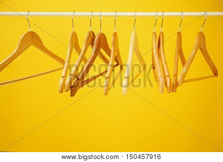 Wooden coat hangers on clothes rail and yellow background