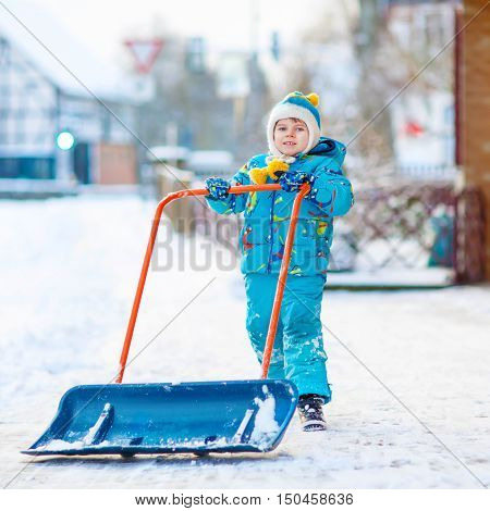 Cute little kid boy in colorful winter clothes having fun with snow shovel, outdoors during snowfall. Active outdoors leisure with children in winter. Happy child with warm hat, hand gloves, winter fashion