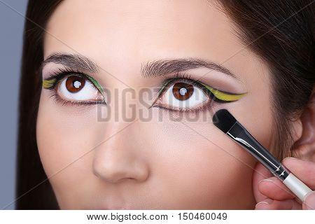 Makeup artist applying makeup on model eyes, close up
