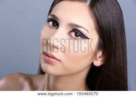 Portrait of young attractive woman with beautiful eye makeup on grey background