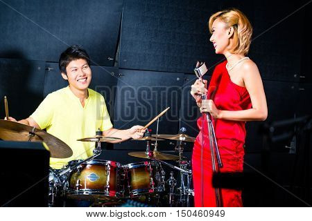 Asian professional singer and drummer recording new song or album CD in studio
