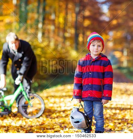 Little kid boy of five years and his father in autumn forest with a bicycle. Active child putting his bike helmet. Safety, sports, leisure with kids concept.