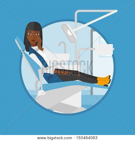An african-american young patient sitting in dental chair. Sad woman suffering from tooth pain. Woman having a toothache. Vector flat design illustration in the circle isolated on background.