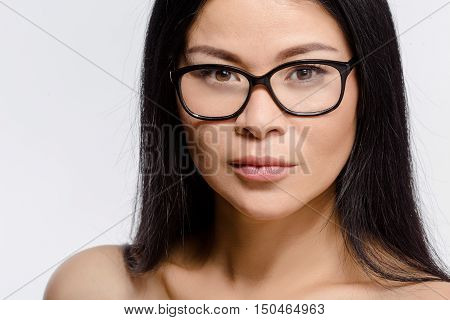 Portrait of beautiful Korean woman posing in glasses in studio. Attractive young lady looking at camera isolated on white background.