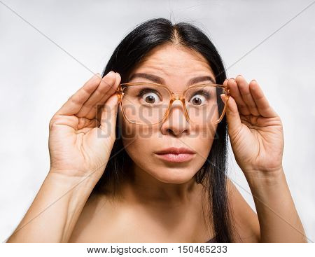 Beautiful Korean woman looking through glasses over white background in studio. Attractive young lady posing for fashion or vogue magazine.