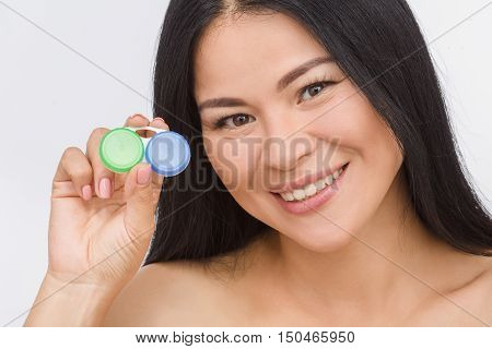 Picture of happy Korean or Asian woman demonstrating container for contact lenses isolated on white background in studio.