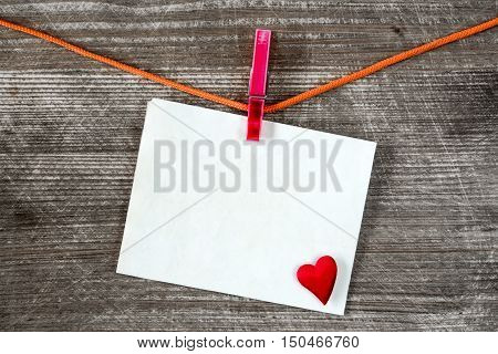 Message and red heart on the clothesline against wooden background