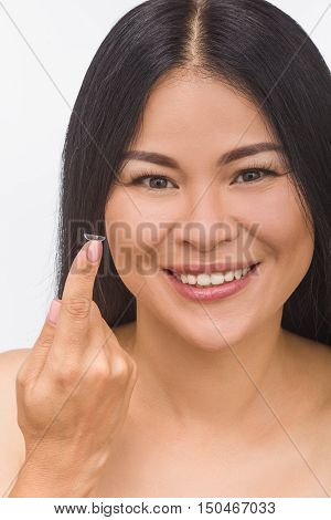 Portrait of happy brunette Korean or Asian woman with contact lenses isolated on white background in studio. Vision concept.