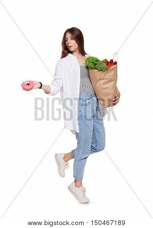 Happy young woman holds shopping paper bag full of groceries, vegetables and fruits and throw away glazed donut, isolated at white background. Healthy food shopping choice. Female buyer