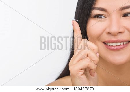 Picture of young Korean or Asian woman demonstrating contact lenses over white background. Beauty, vision, eyesight, ophthalmology and people concepts.