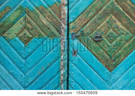 Old wooden turquoise door with a metal handle