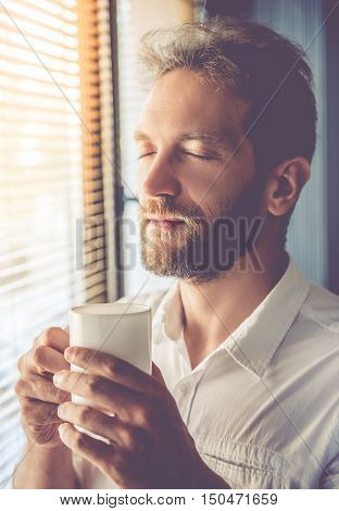 Handsome young businessman is holding a cup of coffee and smiling while standing with closed eyes near the window in his office