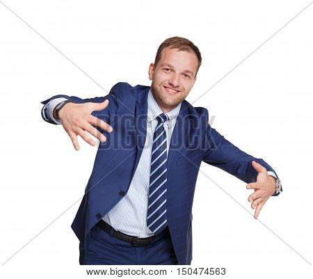 Young smiling businessman shows holding something big with open hands, isolated on white. Portrait of man in trendy blue suit, happy looking at camera