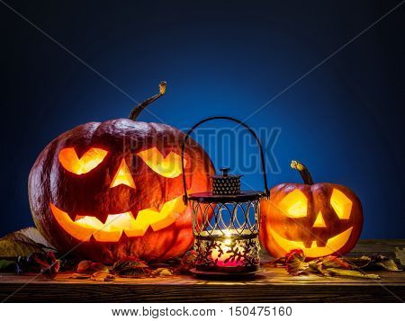 Grinning pumpkin lantern or jack-o'-lantern is one of the symbols of Halloween. Halloween attribute. Wooden and dark blue background.